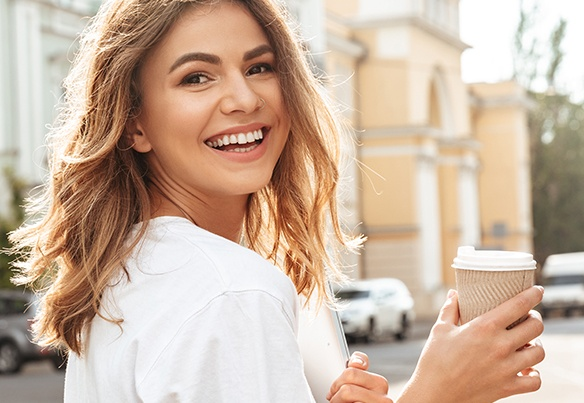 Smiling woman holding coffee to go cup