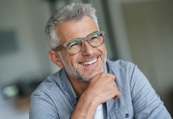 Relaxed older man smiling with gray hair, beard, and glasses