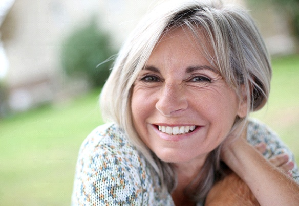 Older woman with gray hair smiling towards the camera in front yard