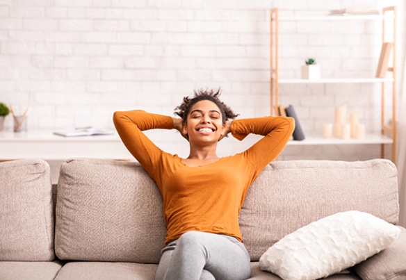 relaxed young woman on couch with arms behind her head