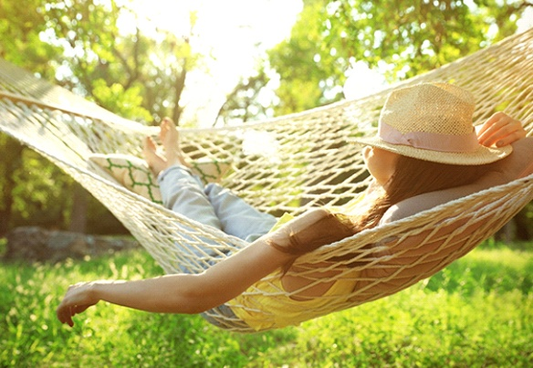 woman relaxing in hammock with hat over her face