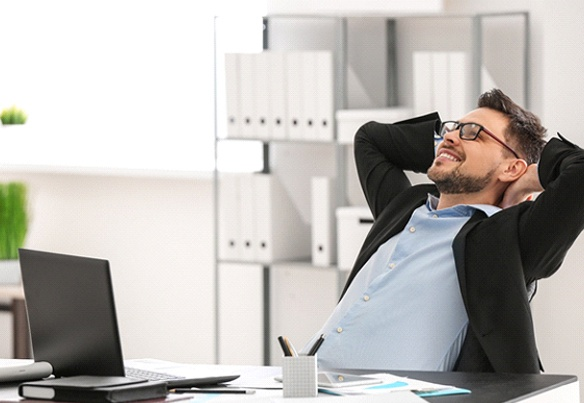 man leaning back and smiling in office
