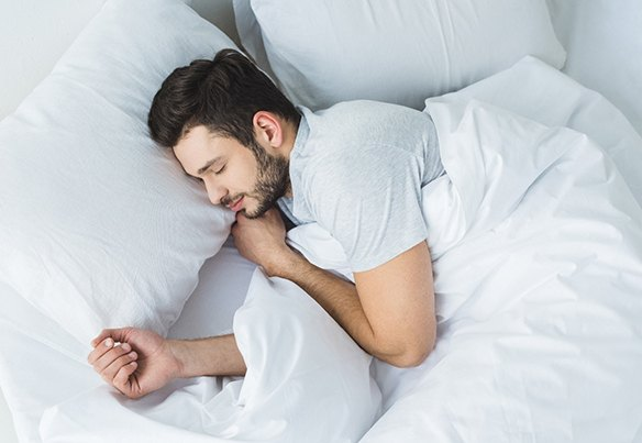 man sleeping peacefully in bed