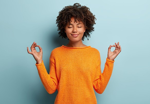 relaxed woman wearing orange sweater