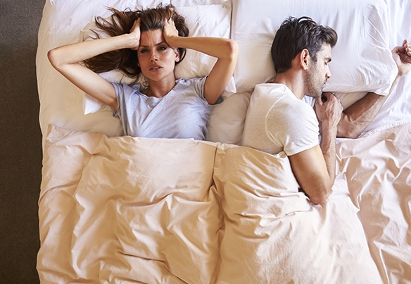 Frustrated woman next to snoring man in bed